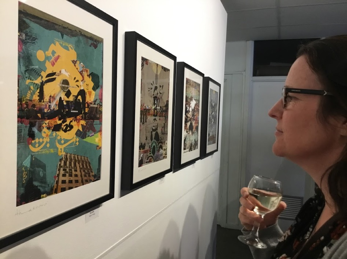 Woman holding wine and looking at aretwork