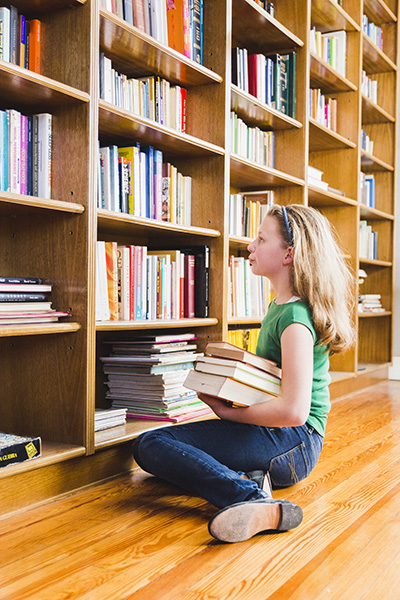Girl sitting holding books and looking at bookshelf full of books