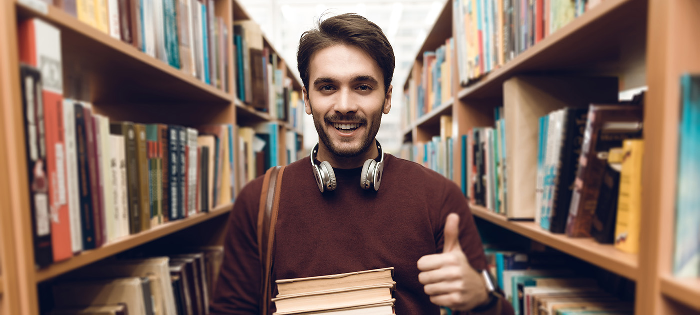 Male student in library aisle holding books and giving thumbs up sign