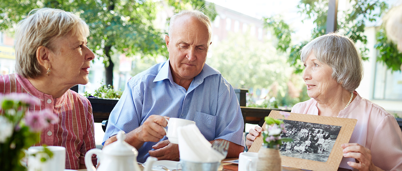 Senior friends gathered together in outdoor cafe and listening attentively to woman in pink blouse with old black-and-white photo in hands
