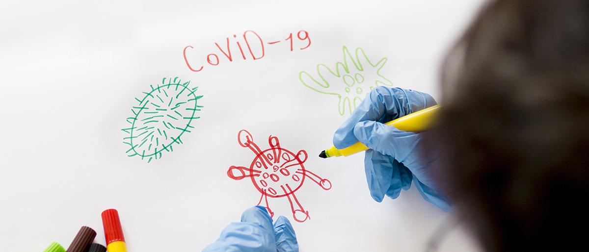 Boy wearing gloves drawing COVID-19 coronavirus