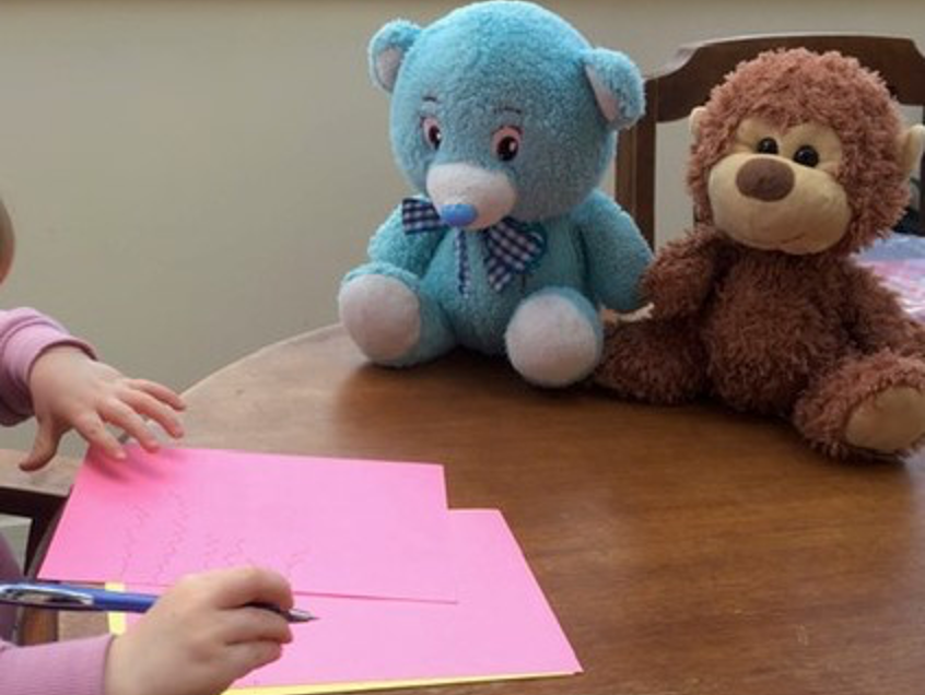 Child drawing on pink paper on desk with sort toys nearby