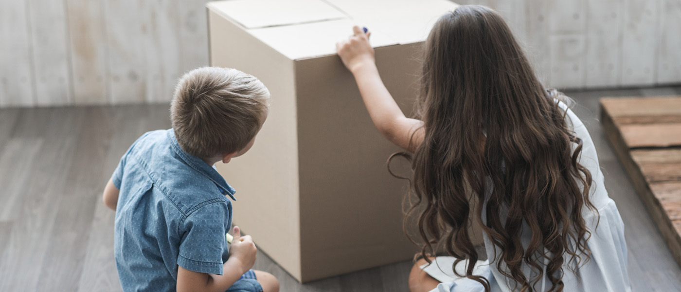 Two children sitting on the floor and drawing on a cardboard box