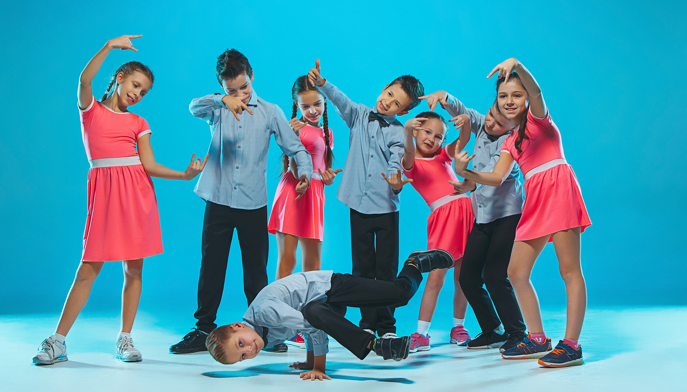 Cute funny girls and boys dancing on blue studio background