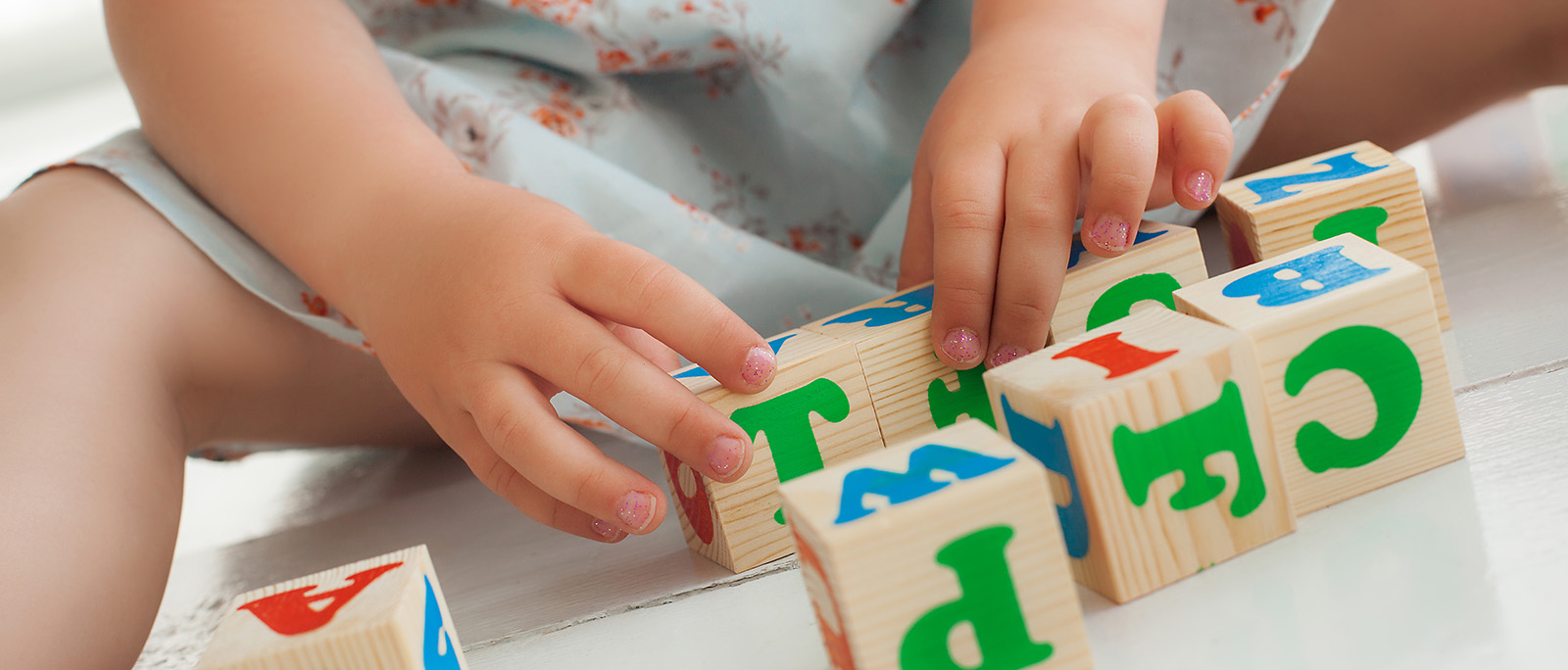 Girl playing with alphabet blocks