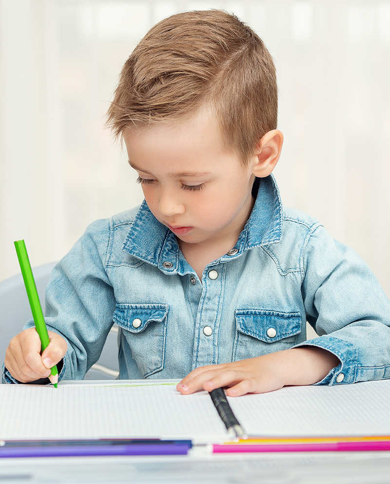 Boy wiriting with green pen on a notepad