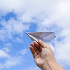 hand with paper plane against blue sky with clouds